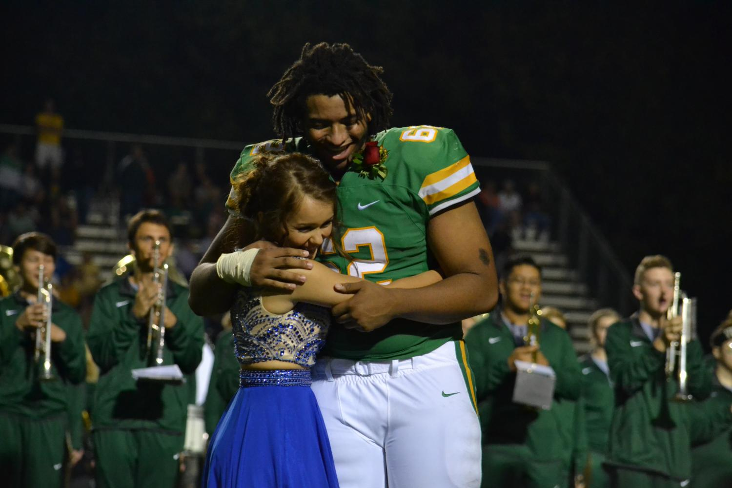 Gutierrez hugs Clark before walking to the middle of the field waiting to hear the name of the homecoming king.