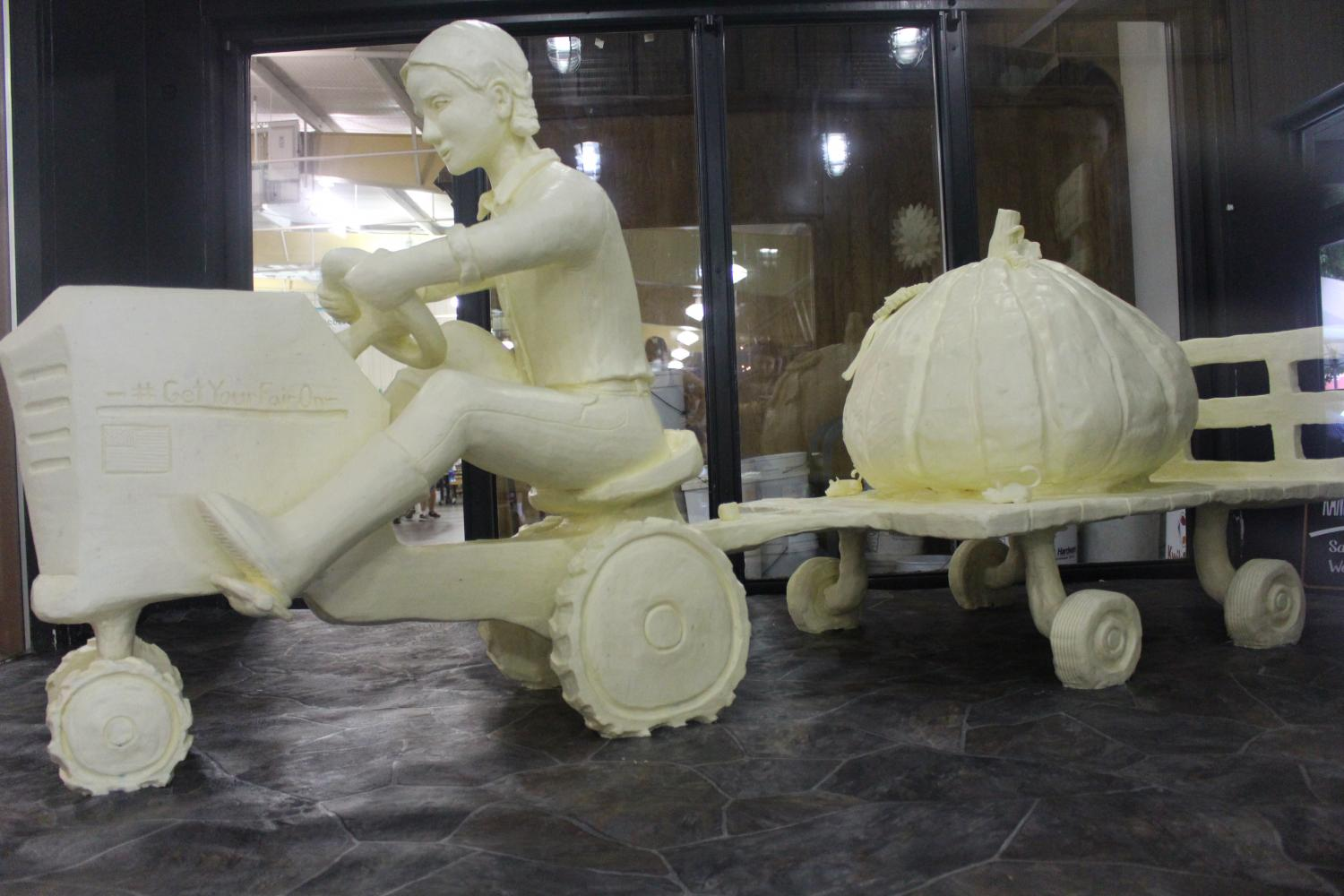 The Kansas State Fair butter sculpture of a girl hauling her first place pumpkin with her tractor. It took up to 1,600 pounds of butter to make this sculpture, and an average of 85 hours took sculpt it.