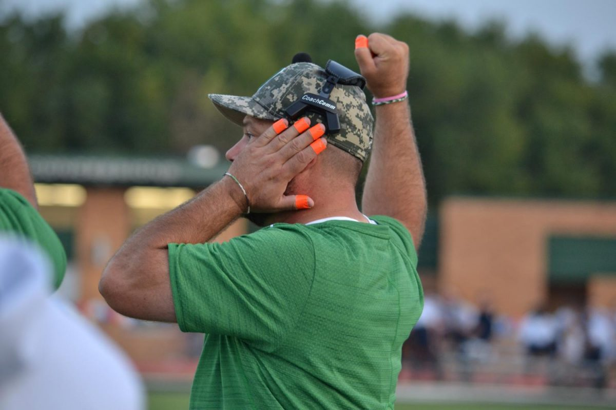 Coach+Olmstead+signaling+to+the+running+backs+on+the+field+during+the+game+against+Maize+Sept.+15.