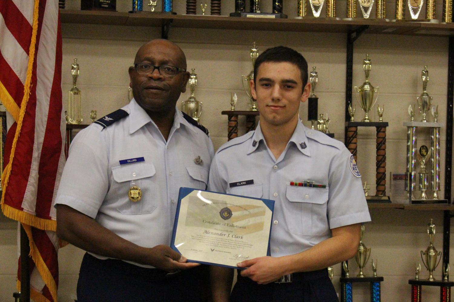 Senior Alexander Clark accepting his Certification of Enlistment from Colonel Michael Dillard