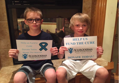 Wyatt (left) and his twin brother, Weston, hold up signs to help find a cure for the Scleroderma foundation.