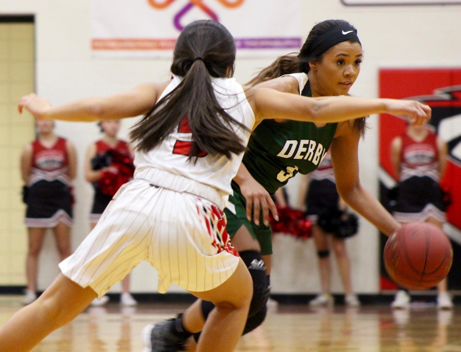 Junior+Aliyah+Meyers+dribbles+the+ball+out+of+her+opponents+reach.