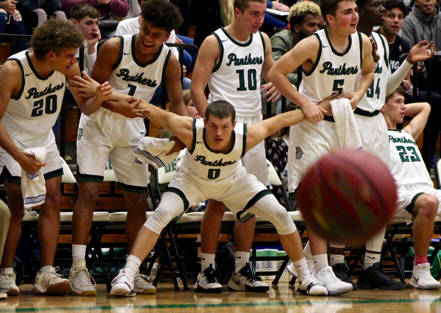 The team holds back junior Dax Benway as he gets excited in the final minutes of the game