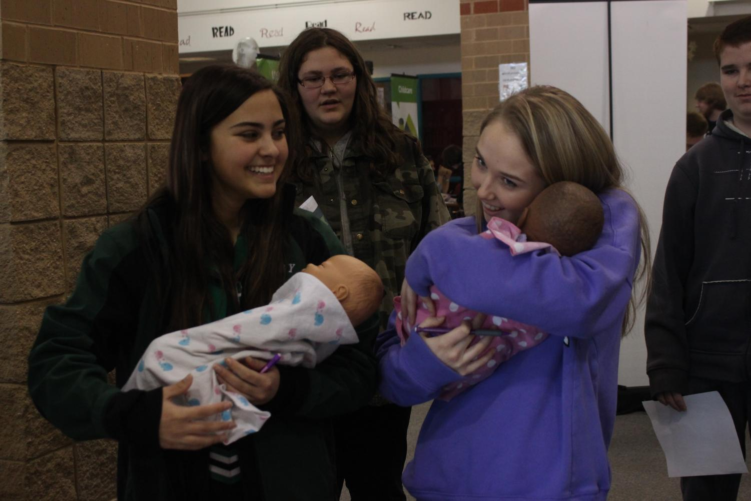Freshman Lauren Amend (left) laughs at freshman Brylee Hull (right) who was trying to get the mechanical baby to stop crying.