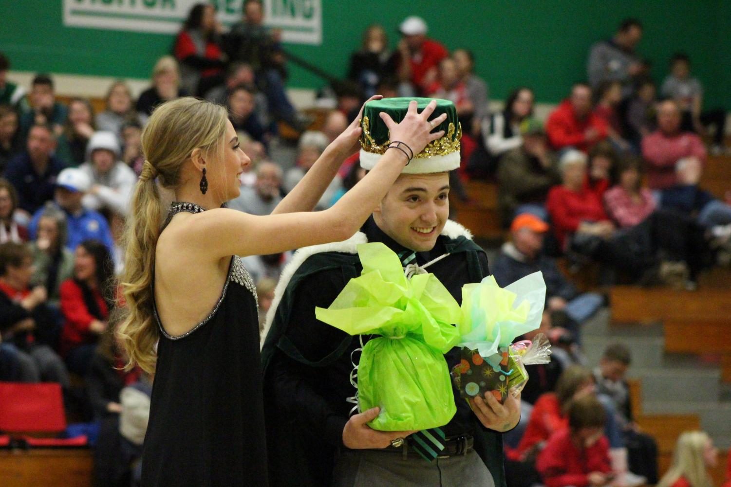 Senior Taylor Silva readjusts the crown on senior Brett Westerman's head.
