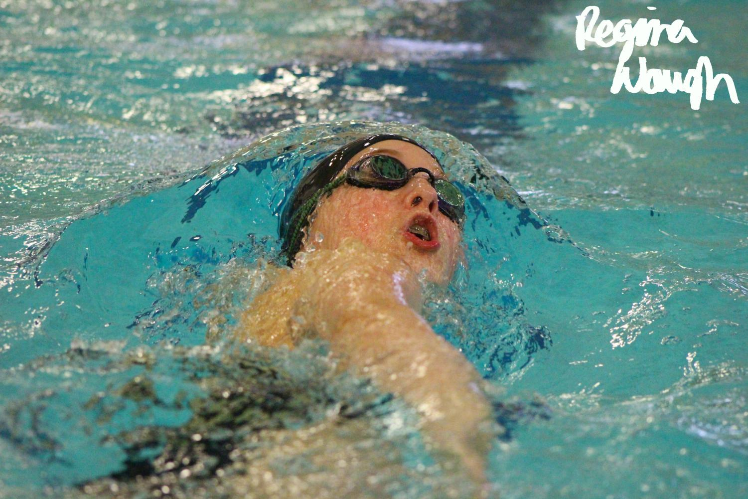 Sophomore+Addi+Karsak+coming+up+to+the+surface+of+the+water+while+swimming+backstroke.