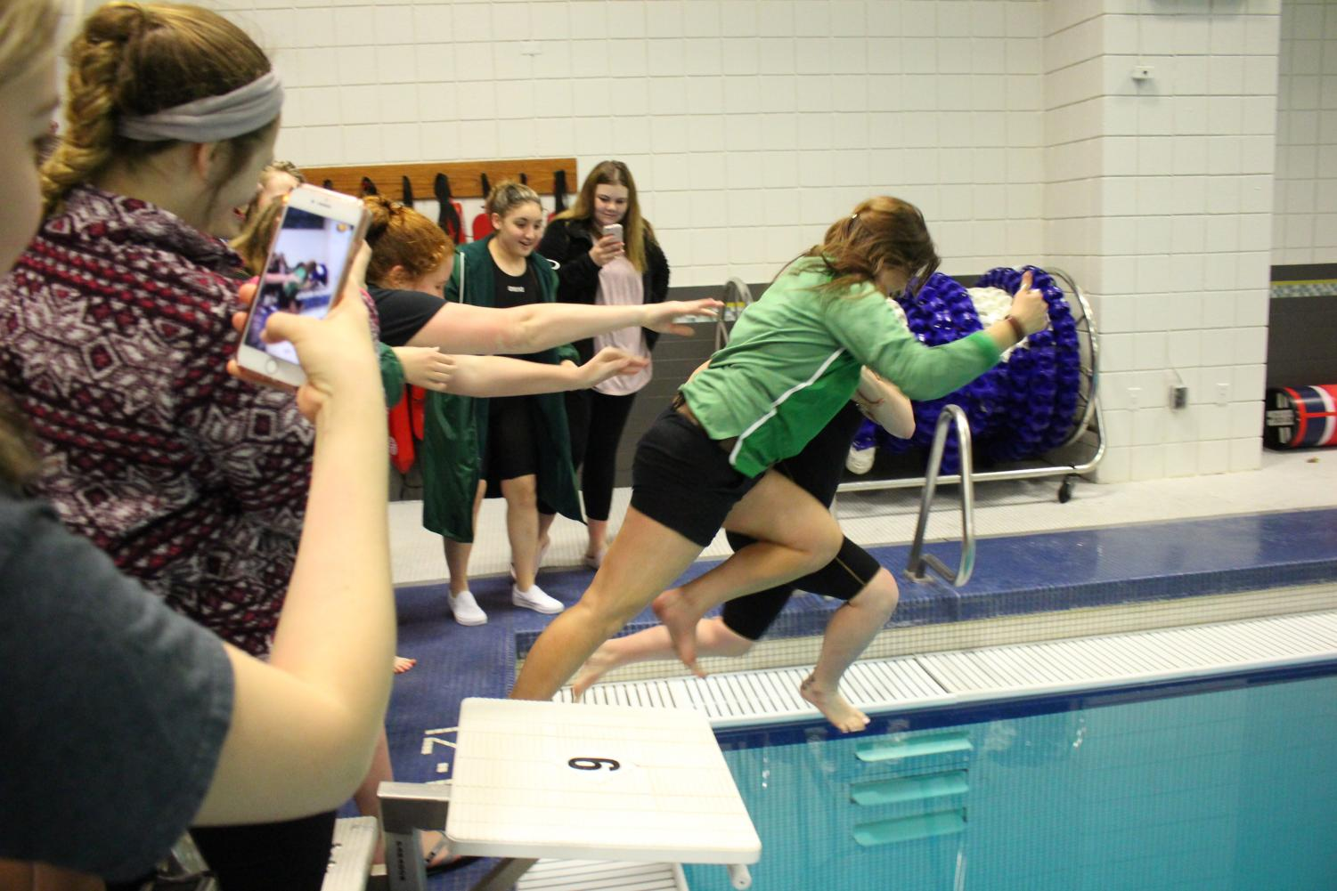 The+girls+swim+team+pushes+Coach+Queen+into+the+pool.+It+is+a+tradition+to+throw+Queen+into+the+pool+if+they+win+first+place+at+the+home+meet.