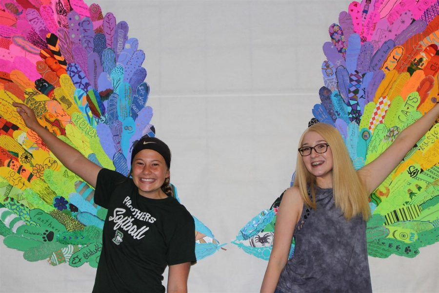 Sophomores Grace Shoemaker and Alyssa Dooms smile in front of the art installation.