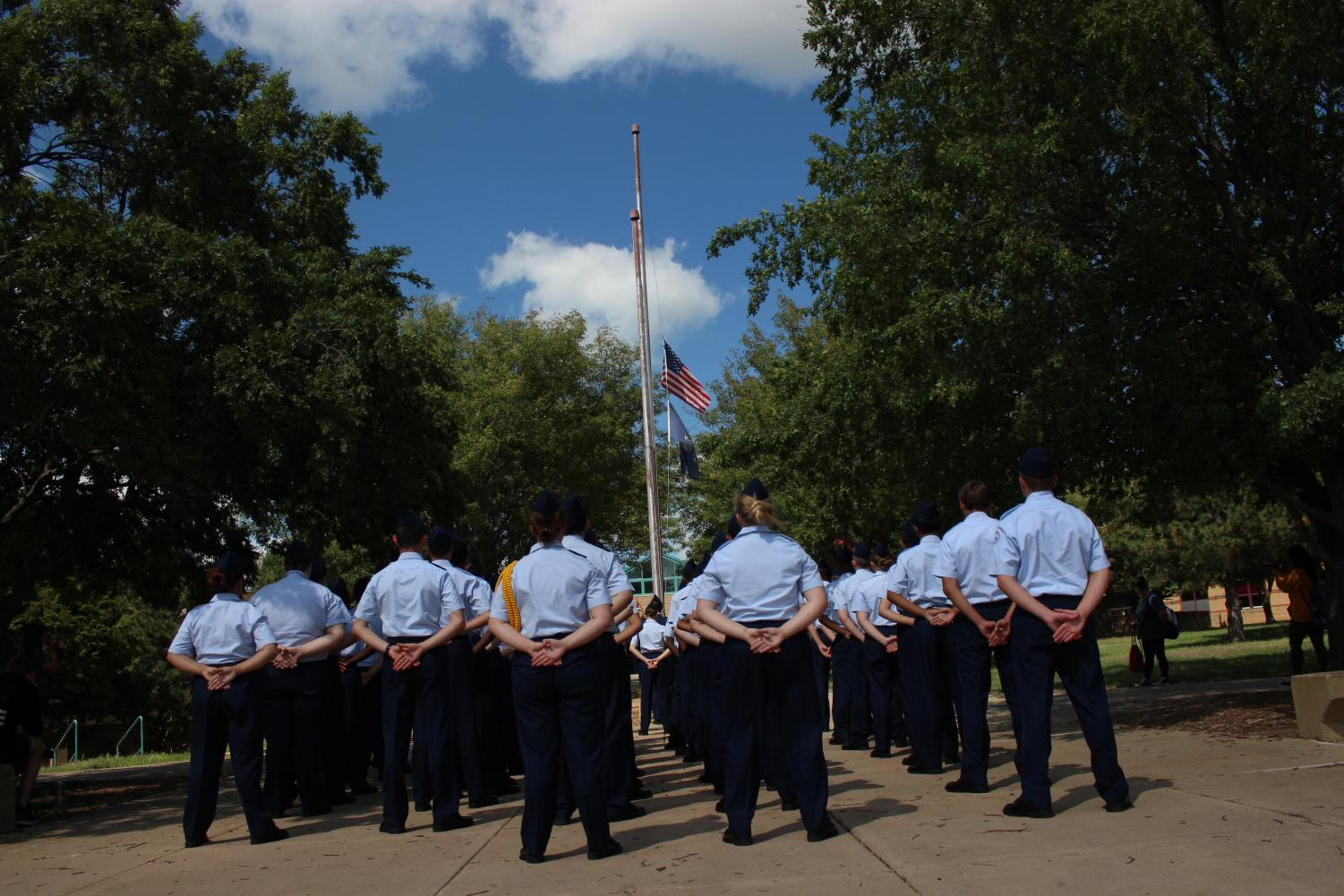 AFJROTC students stand in formation while giving a moment of silence.