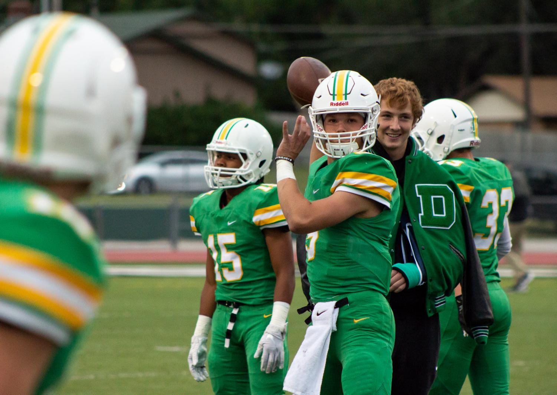 Senior Hunter Igo prepares to throw a pass as junior Grant Adler watches from behind. Igo is filling in as quarterback for Adler.