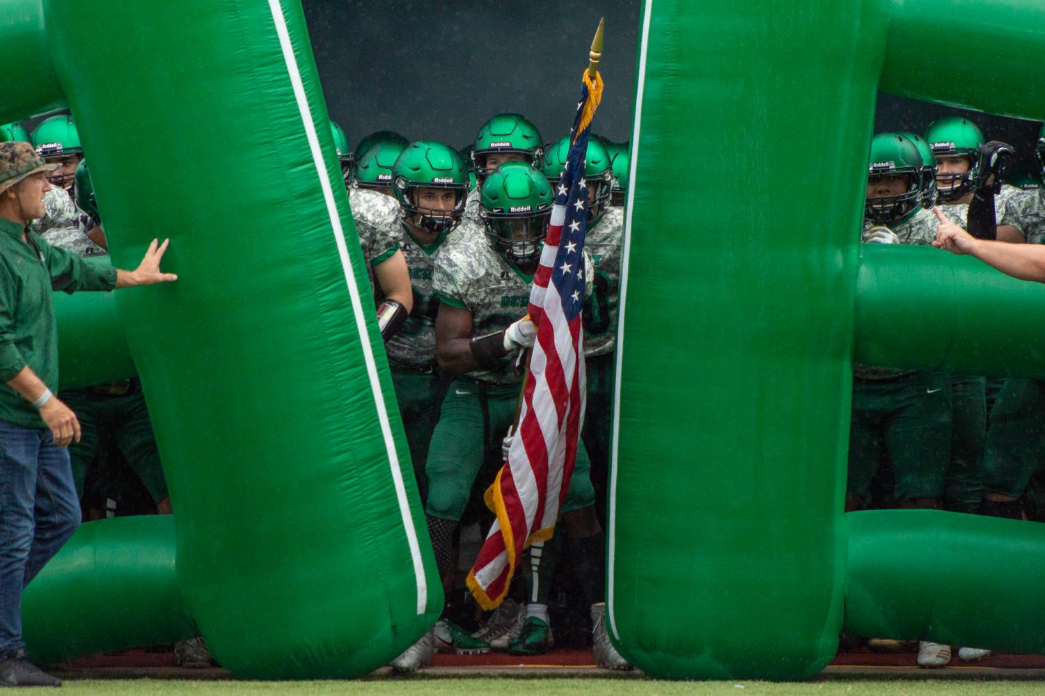 Senior Ejavion Fisher holds the American Flag as his team waits to be released out of the helmet tunnel. Photo by Regina Waugh