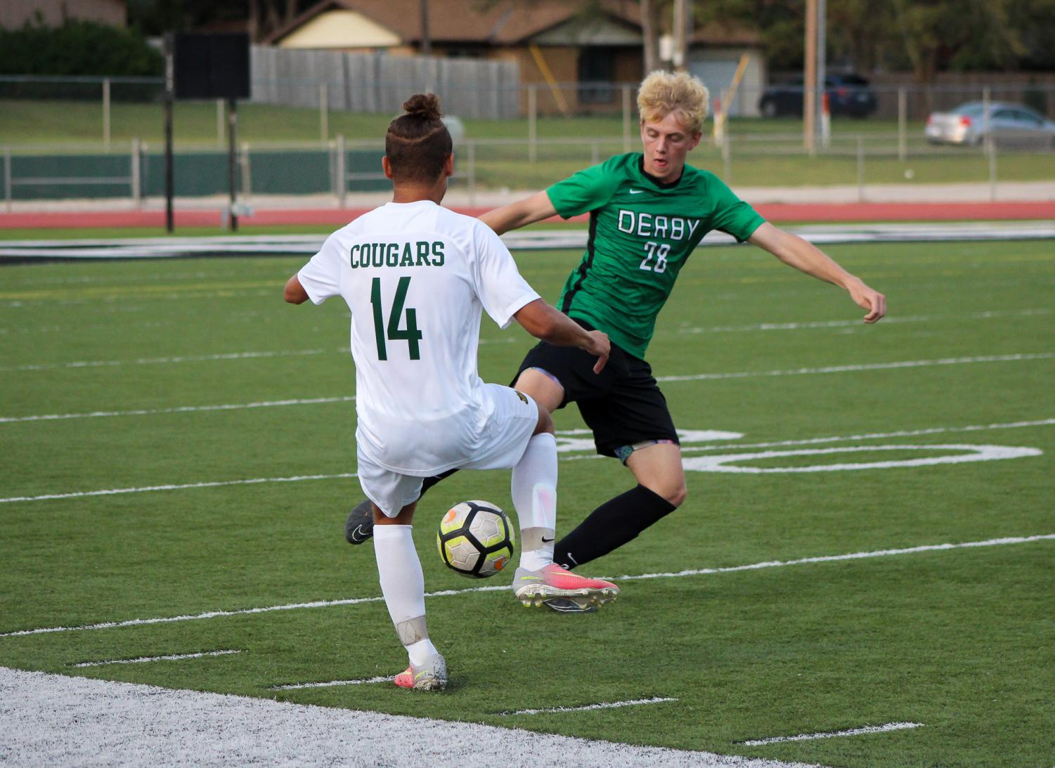 Junior Matthew Young kicks the ball away from his  opponent.