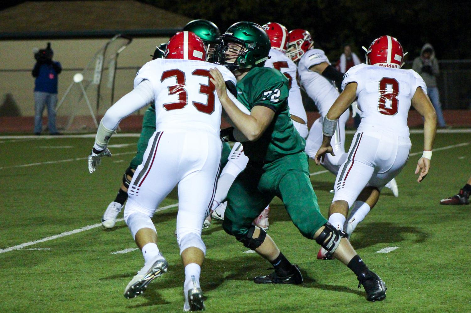Senior+Bryce+Atkinson+pushes+his+opponent+away+from+the+ball+carrier.