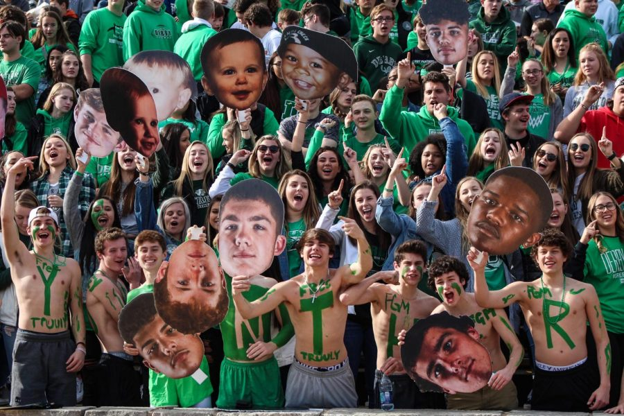 The student sections cheers while holding up fatheads of football seniors.