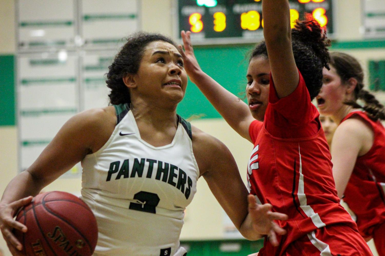 Senior Aliyah Meyers protects the ball from her opponent as she goes for a layup.