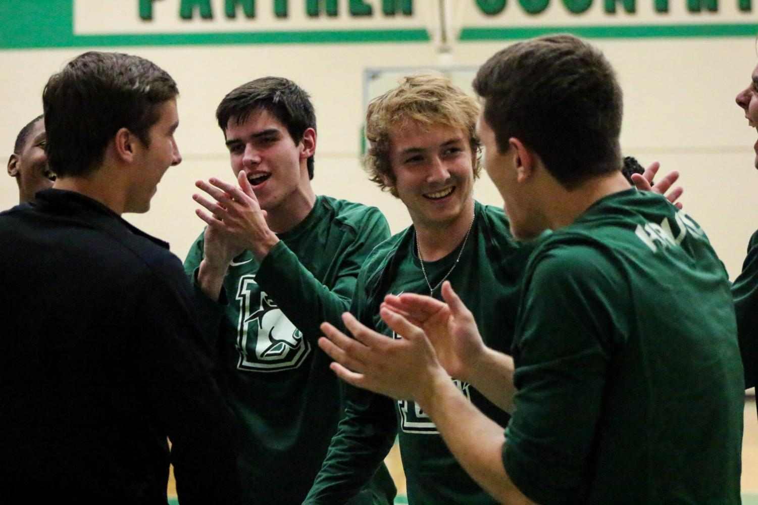The boys basketball team laughs during their pregame warmup.