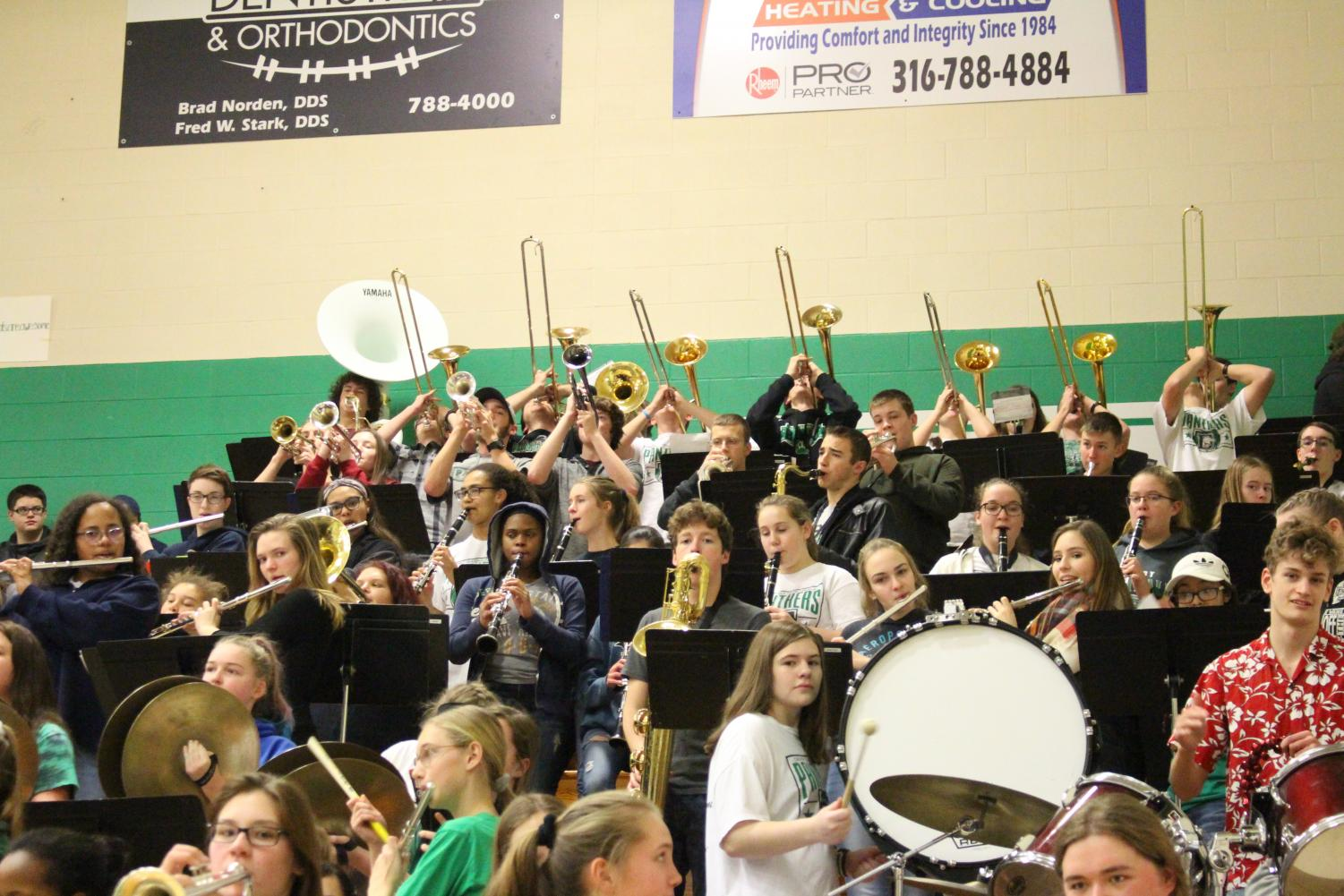 Trombone+players+raise+their+instruments+in+sync+to+pep+music
