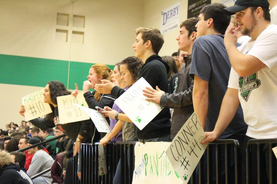 Seniors+Regina+Waugh+and+Promise+Asher+cheer+along+with+the+rest+of+the+crowd%2C+holding+signs