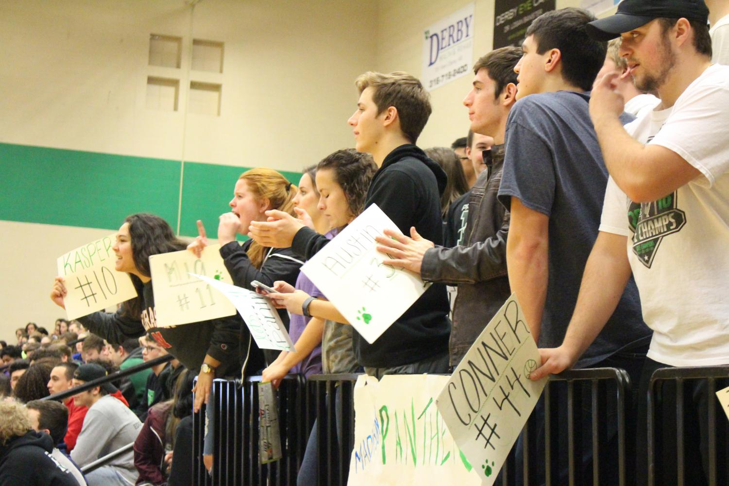Seniors Regina Waugh and Promise Asher cheer along with the rest of the crowd, holding signs
