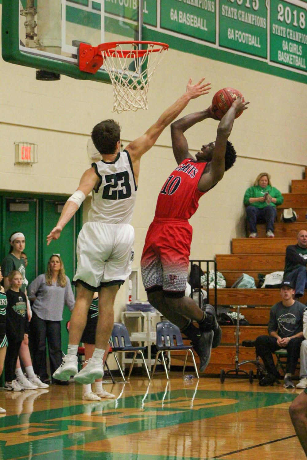 Senior Clayton Hood jumps into the air to block a shot from his Heights opponent.