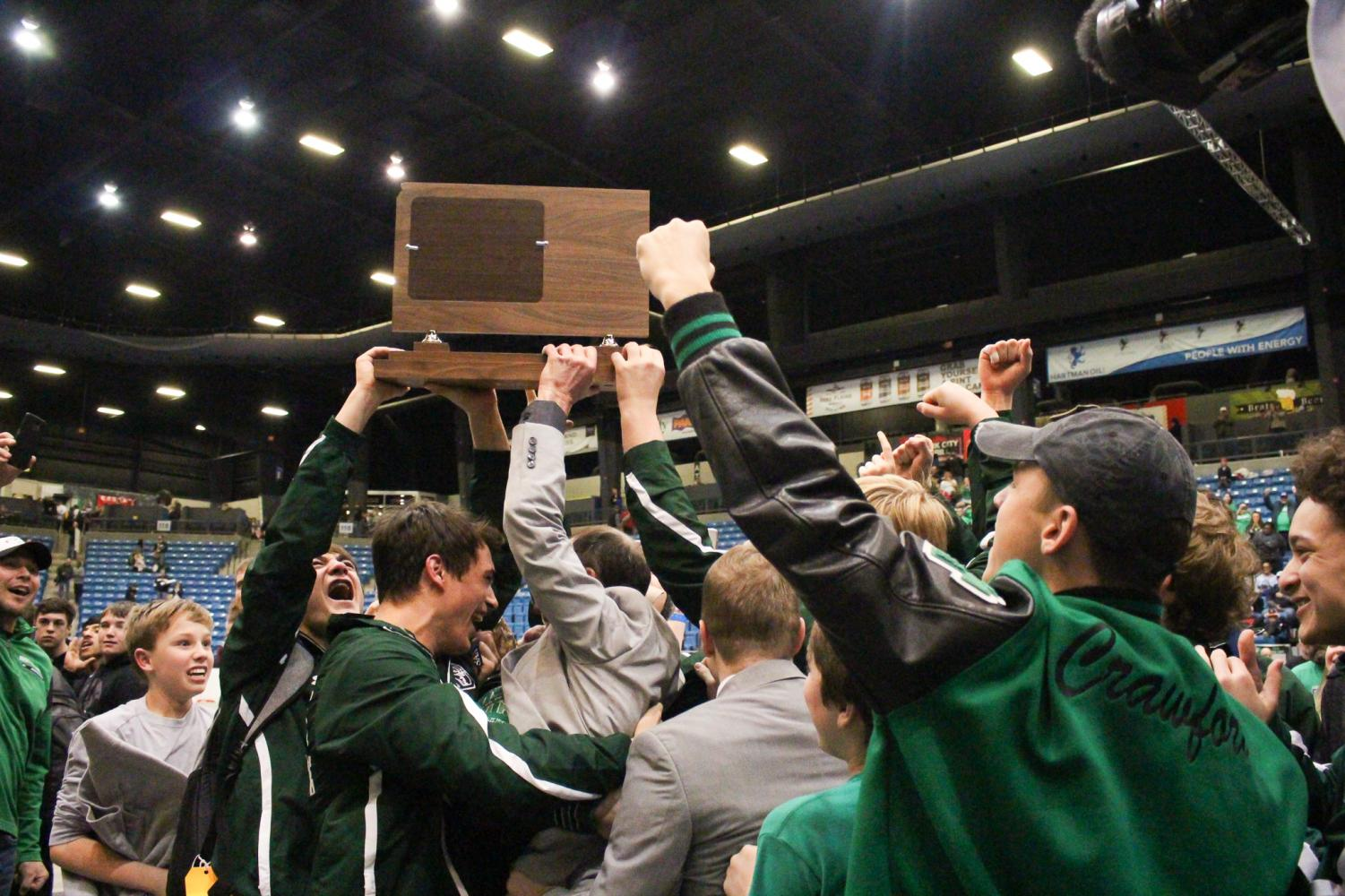 The Derby Wrestling team and it's coaches raise the class 6A state championship trophy. The last time Derby Wrestling won a state title was in 1986.
