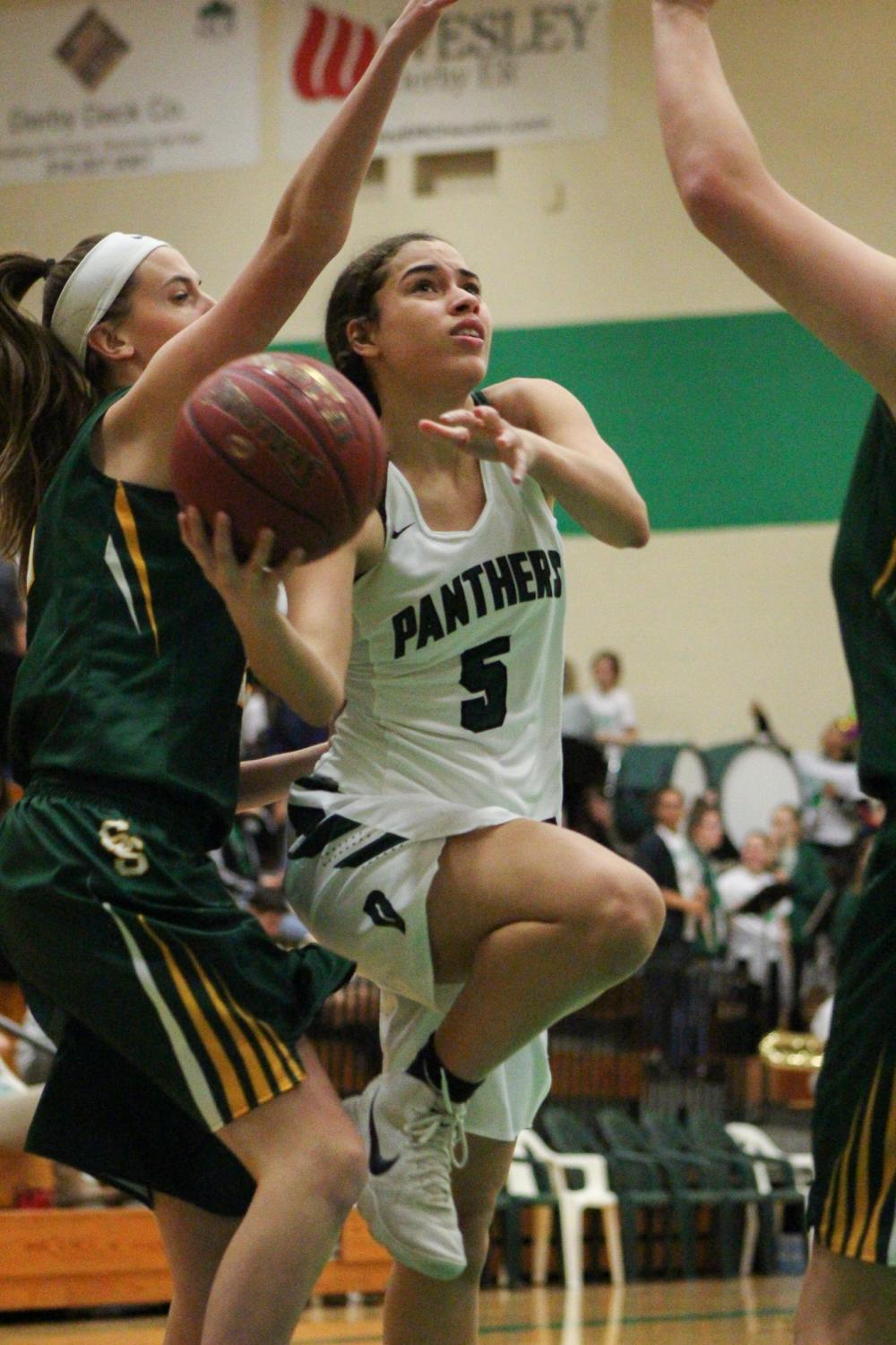 Sophomore Katelyn Kennedy maneuvers around Salina South's defense for a layup. The Panthers defeated the Cougars 57-17.