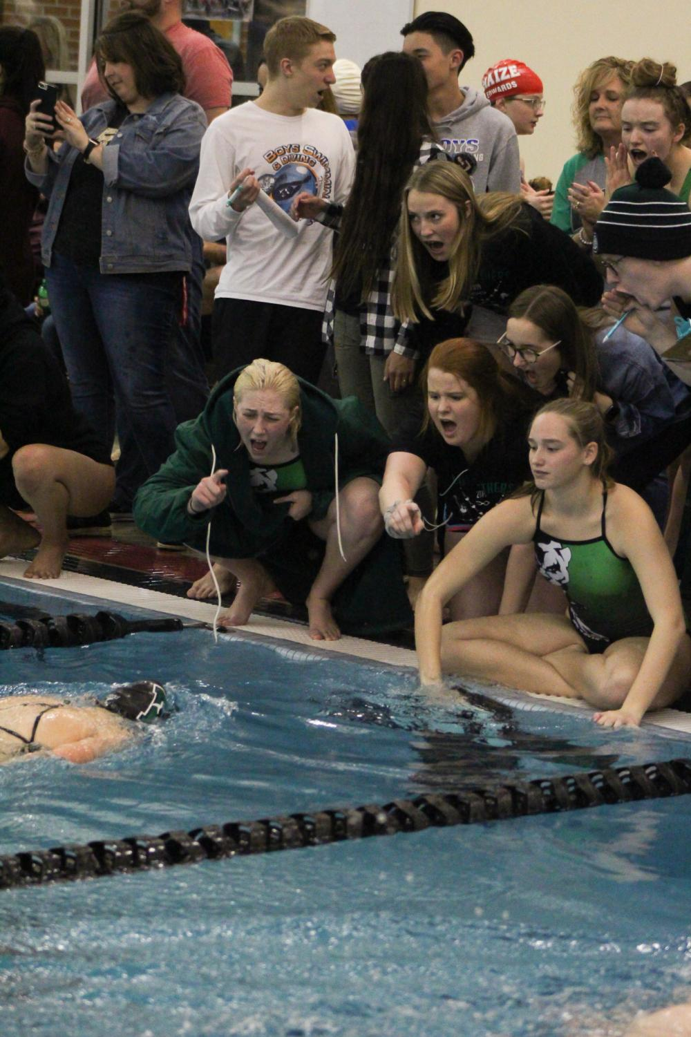 The+girls+swim+team+cheers+on+junior+Jessica+Keasey+during+the+500+yard+freestyle