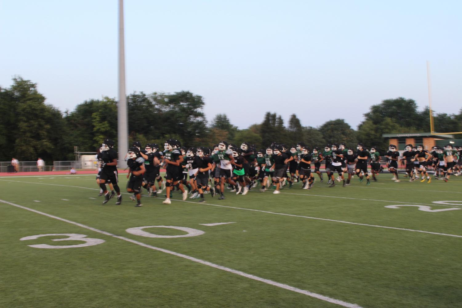 Derby High School Panthers run out onto the field for the last hour of the night.