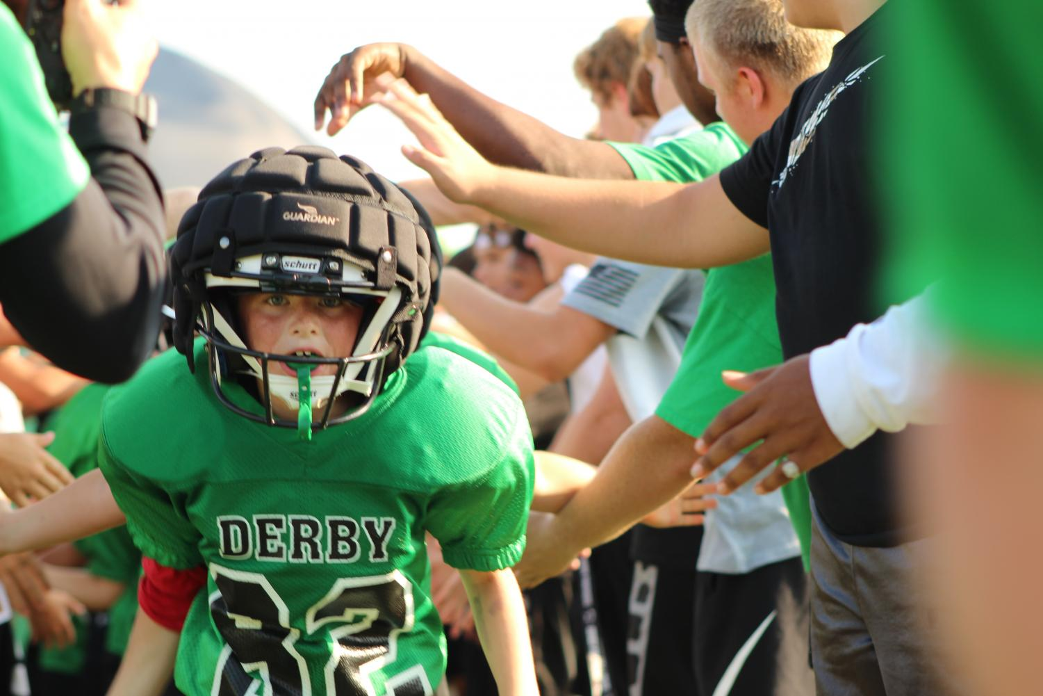 Derby Jr. Football kids run through the tunnel to mark the beginning of their game.