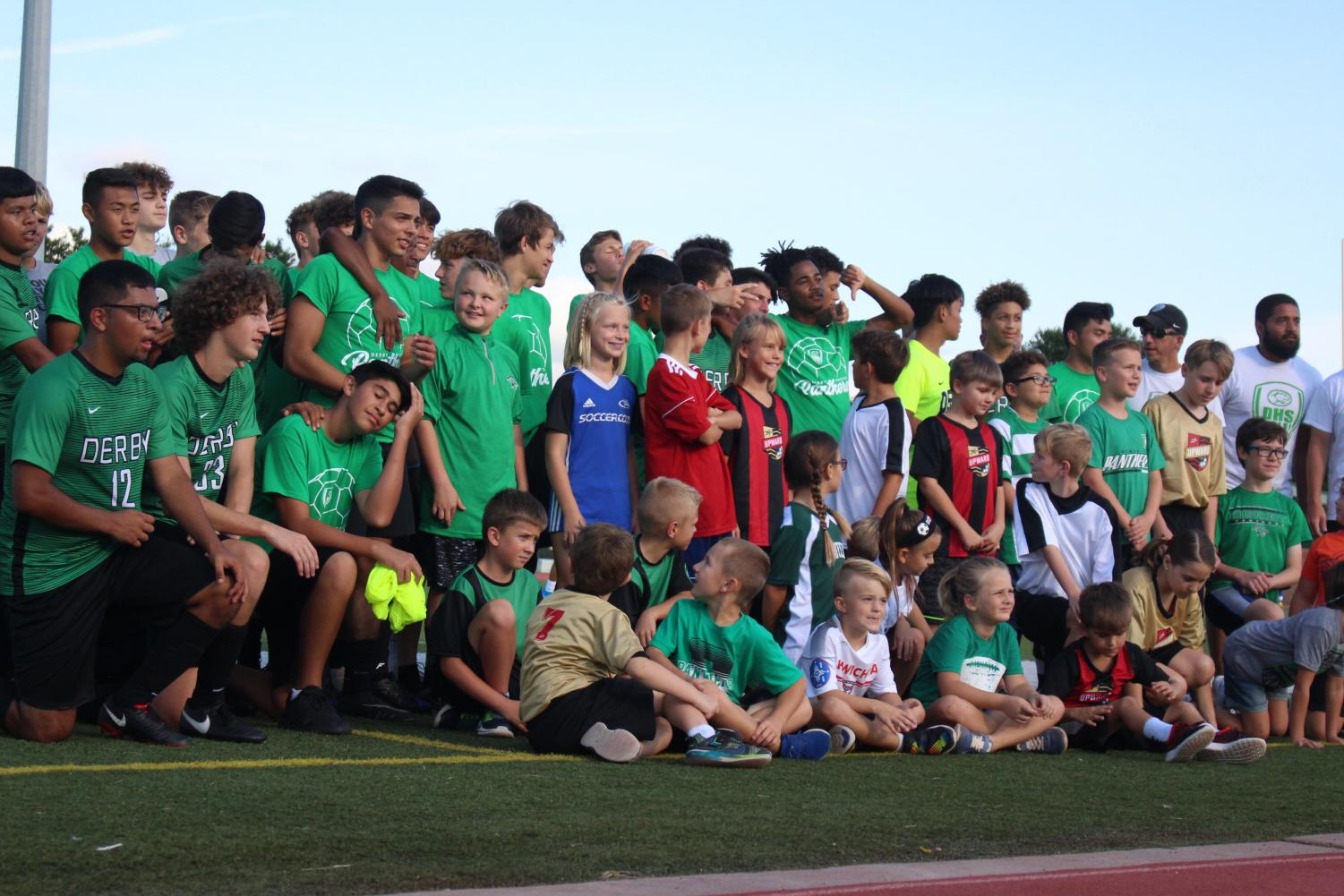 Derby+Soccer+team+gathers+together+with+young+league+to+take+a+picture+before+the+game.