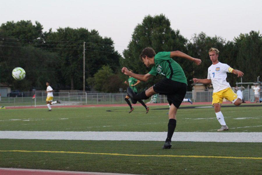 Derby+player+kicks+ball+as+it+approaches+him.