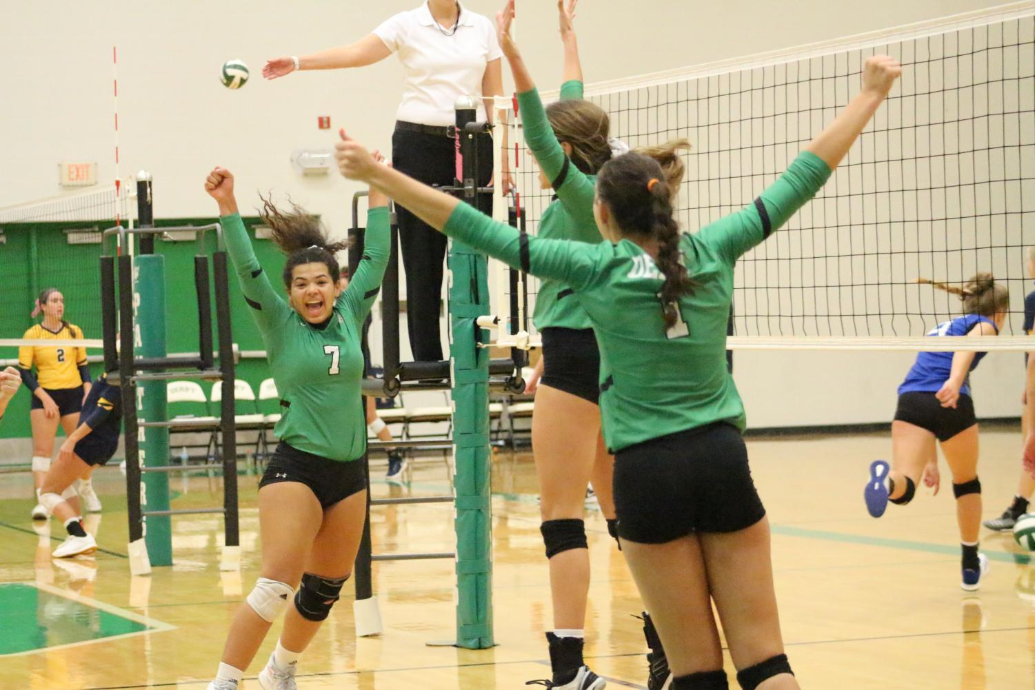 Senior Jalen Keener (left), junior Lexi Pitts (middle) and senior Sydney Nilles (right) celebrate the winning point  in the first set against Washburn Rural