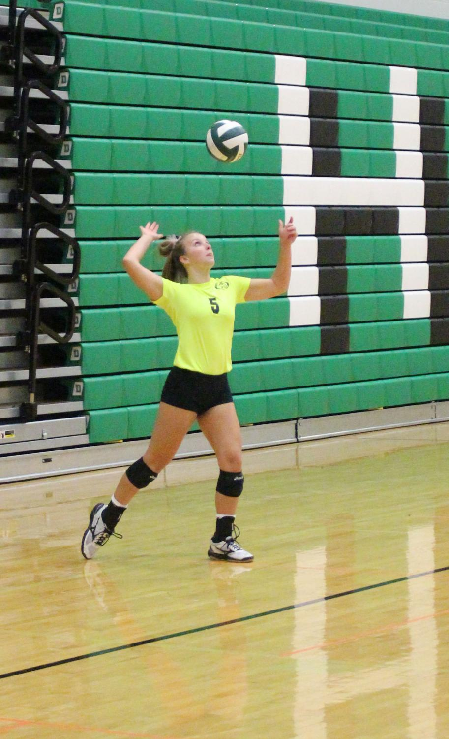 Senior heather Mills Serves the ball across the court.
