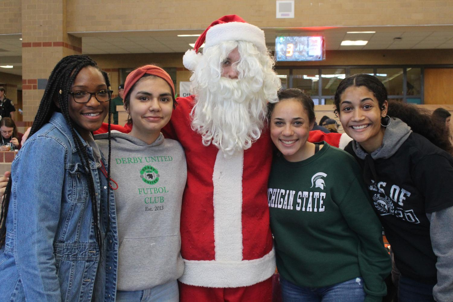 Juniors Aneesa Abdul Hameed, Daizy Treto, Gianni Roland, and Shi'Amber Boyer pose with Santa
