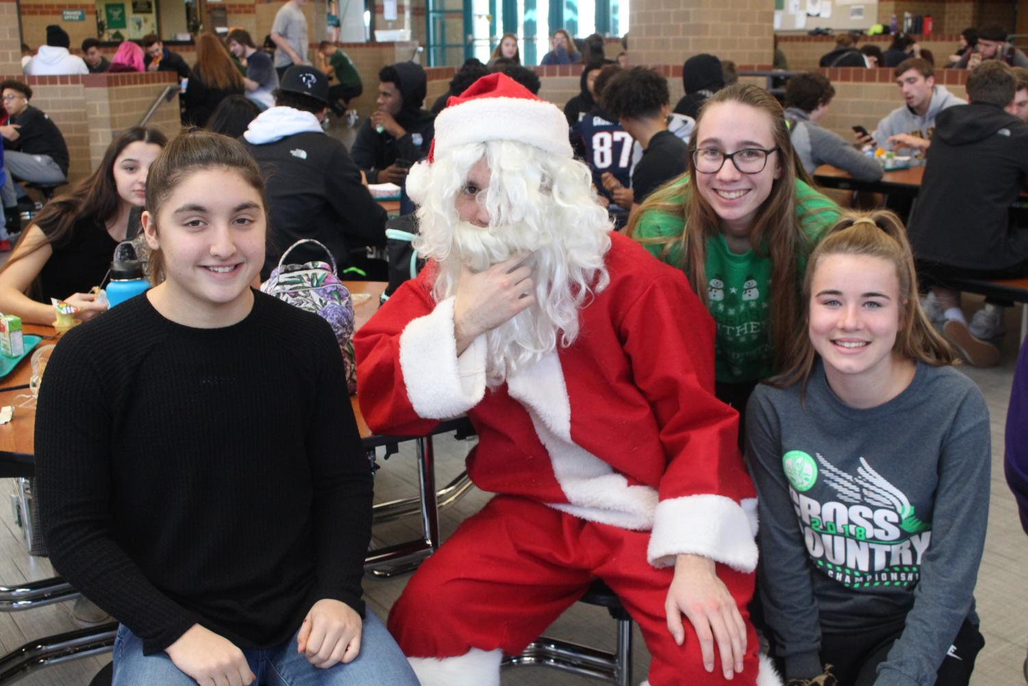 Juniors+Sophia+DeGregorio+and+Ashlyn+Struble+and+senior+Sadie+Svymbersky+pose+for+a+photo+with+Santa.
