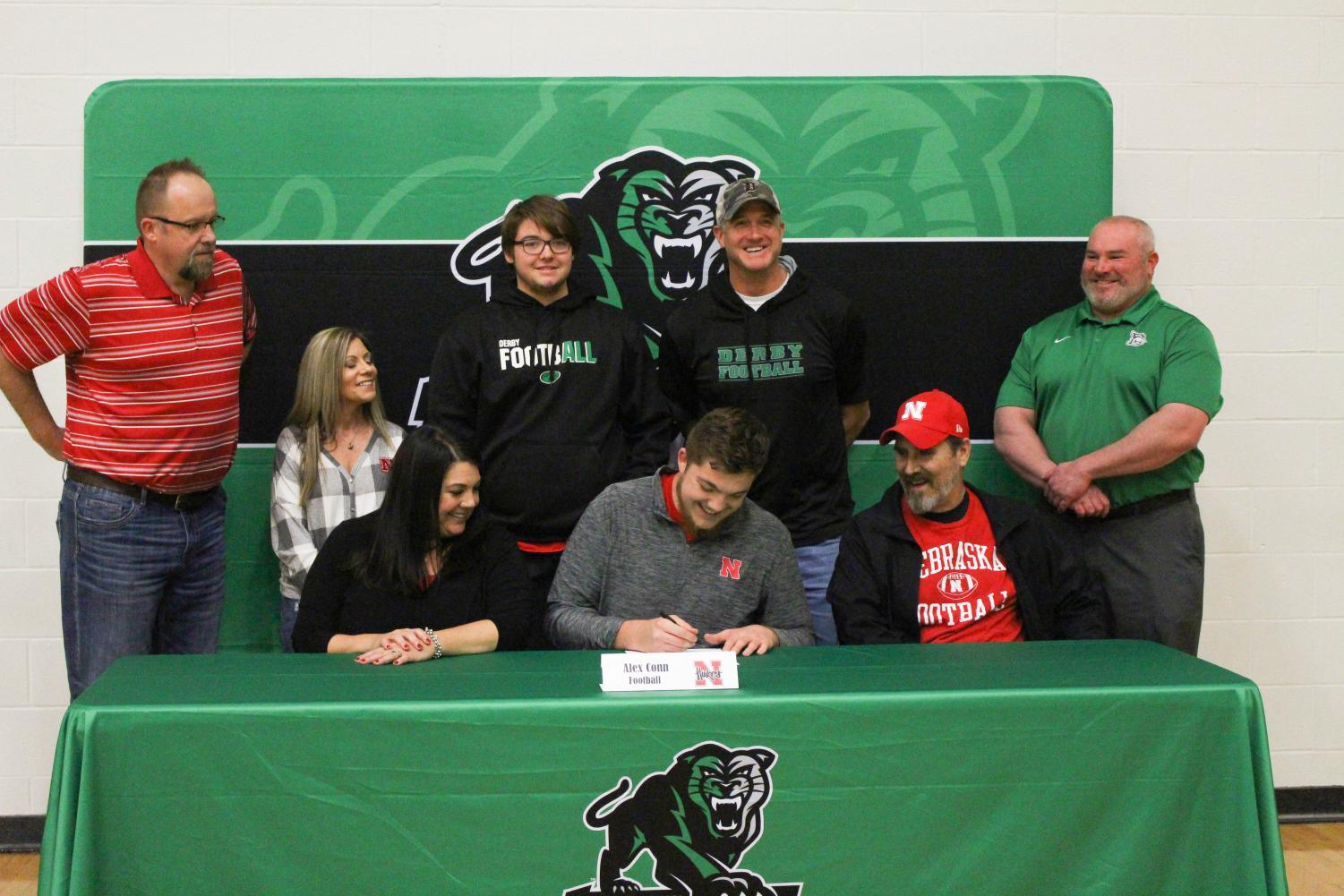 Alex+Conn+mock+signing+to+the+University+of+Nebraska+with+his+family+and+coaches