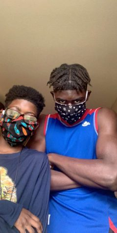 Freshman Samuel Same Ndoumbe poses with his little brother Thomas while wearing their masks.