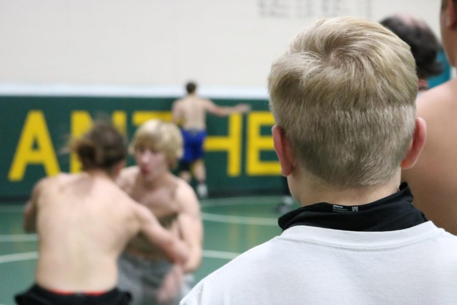 Two boys wrestle while others watch.